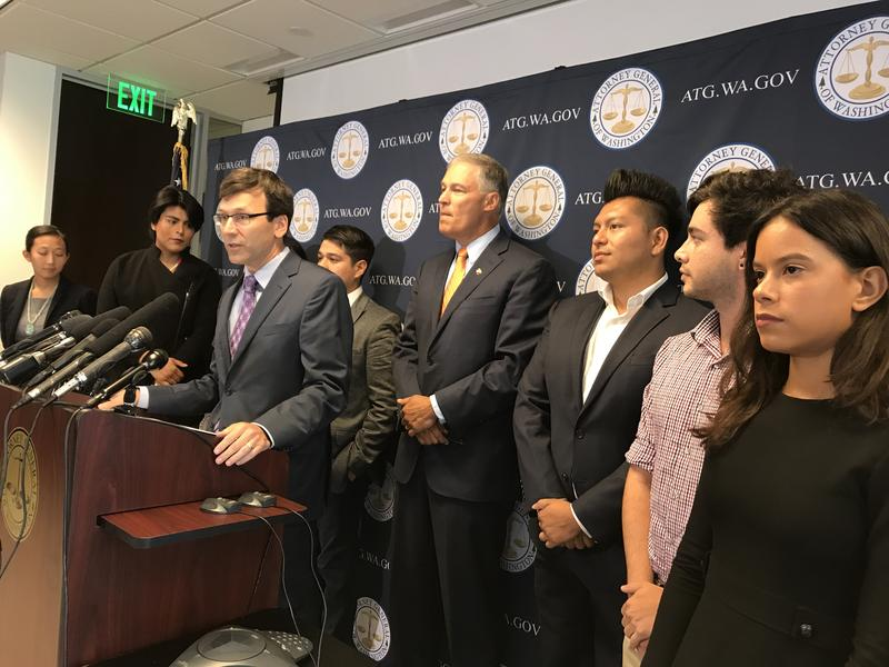 Attorney General Bob Ferguson and Gov. Jay Inslee of Washington state, surrounded by DACA recipients, denounce the Trump Administration's plan to end the federal protection program for young immigrants.