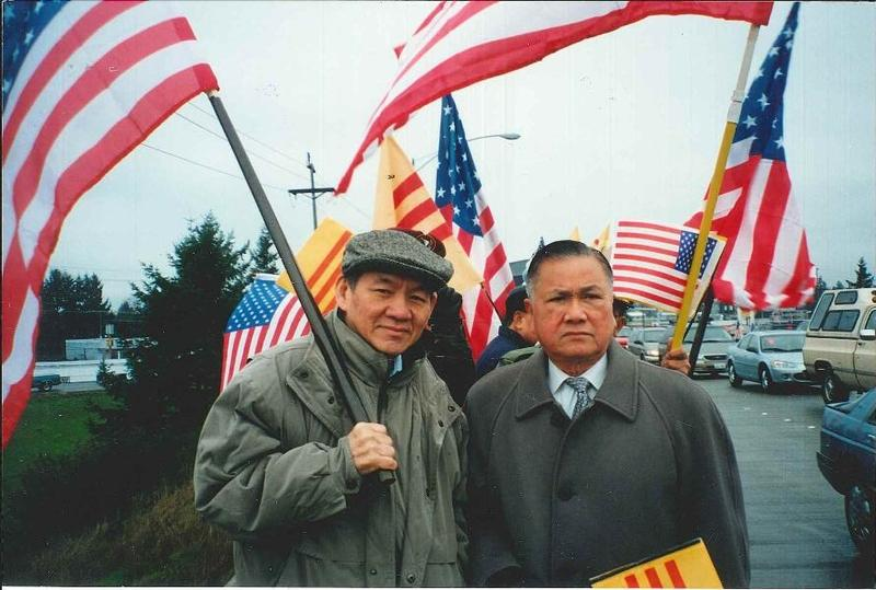 Thanh's father, Duc Tan, holds the American flag and stands next to Dr. Dung Nguyen, president of the Vietnamese Community of Pierce County, at a political rally in this undated photo. Like most other refugees, they still prefer to recognize the flag of t
