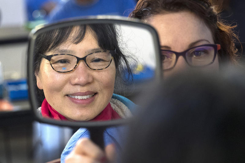 Zhen Zeng tries on a new pair of glasses during the Seattle/King County Clinic on Thursday, October 26, 2017, at Key Arena in Seattle. Zeng waited in line starting at 11 p.m on Wednesday night.