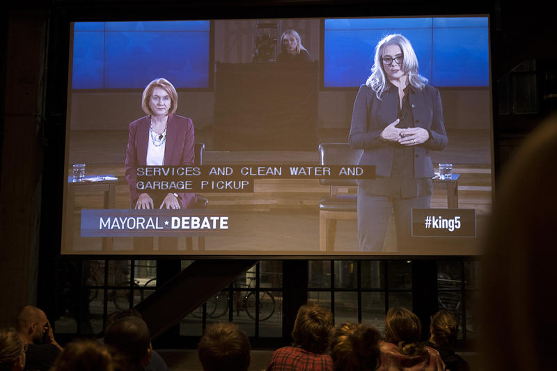 Mayoral candidates Jenny Durkan, left, and Cary Moon are shown on a screen during a mayoral debate viewing party on Tuesday, October 24, 2017, at Optimism Brewing Company in Seattle.