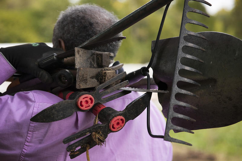 Aregay Desta carries an assortment of tools after a morning of work on Friday, October 13, 2017, at the Rainier Beach Urban Farm and Wetlands in Seattle.