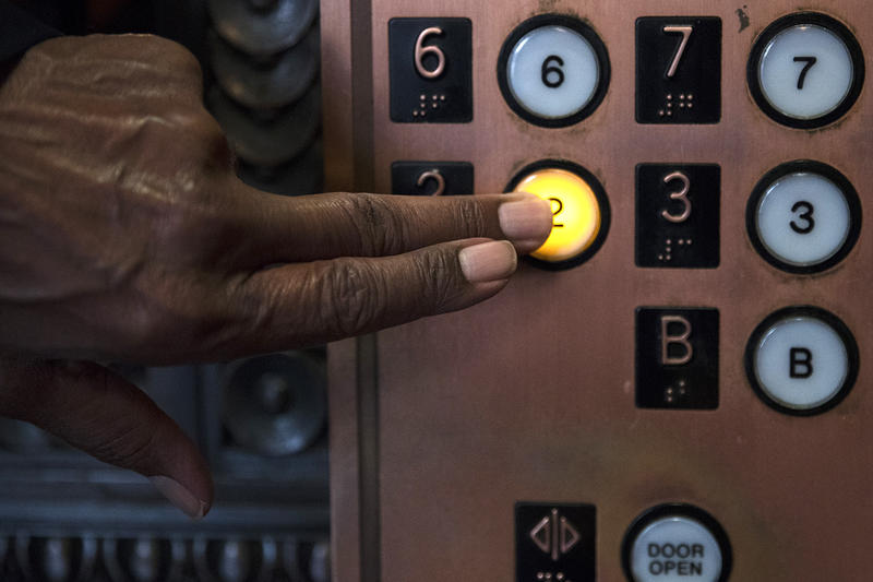 Hamilton Beale operates an elevator in the lobby of Smith Tower on Wednesday, October 18, 2017, in Seattle. Beale has been operating elevators at Smith Tower for 19 years.