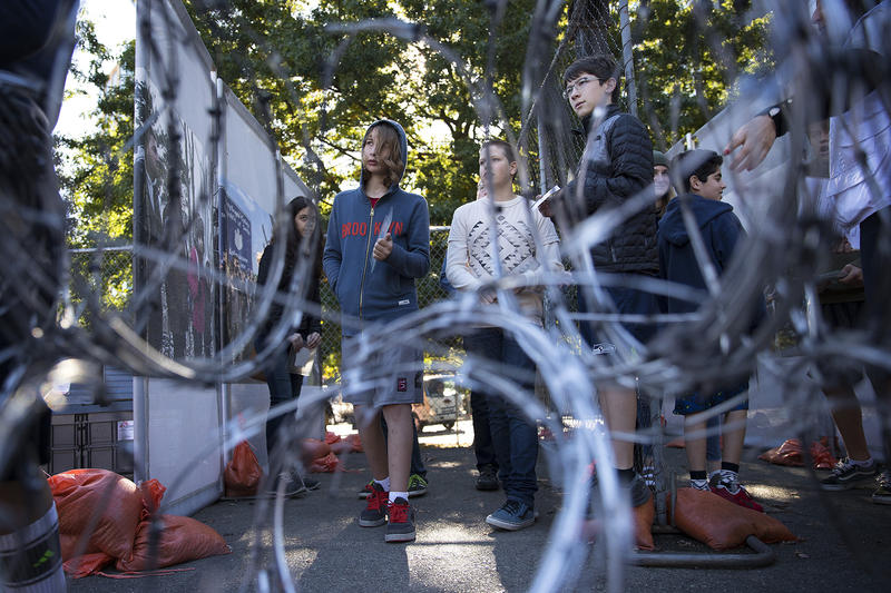 Morningside Academy 8th-grade student Ian Bell, center, is shown through barbed wire fence at the Forced From Home exhibit on Tuesday, October 3, 2017, at the South Lake Union Discovery Center in Seattle.