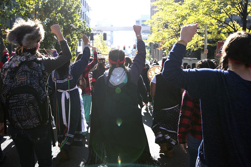 People raise their fists in the air as they march from Westlake Park to Seattle City Hall during the Indigenous Peoples' Day march and celebration on Monday, October 9, 2017, in Seattle.