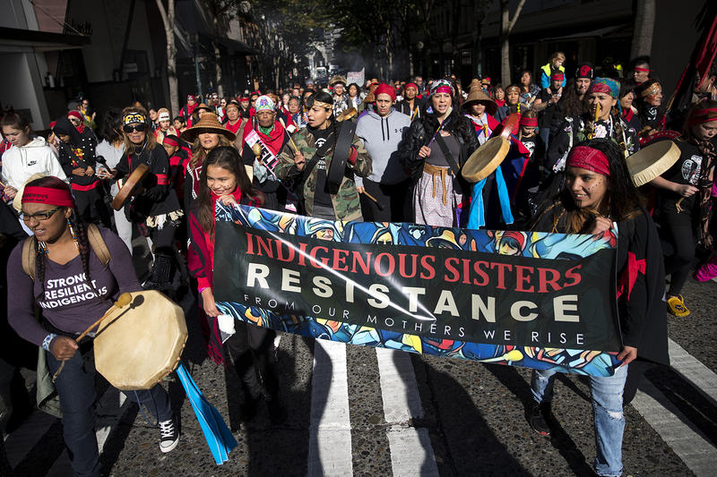 A large group marches toward Seattle City Hall during the Indigenous Peoples' Day march and celebration on Monday, October 9, 2017, in Seattle.