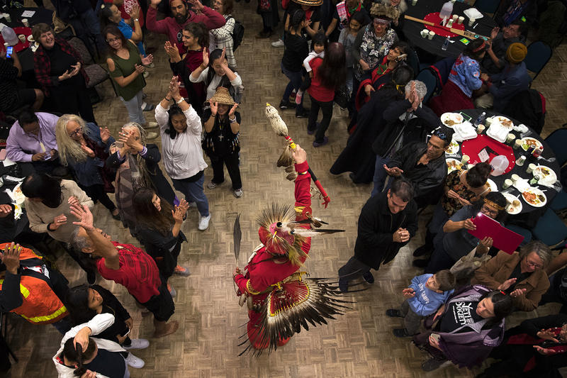 Nikk Dakota, center, of the Turtle Mountain Chippewa Tribe dances as people surround him during the Indigenous Peoples' Day Celebration at Daybreak Star Cultural Center on Monday, October 9, 2017, in Seattle.