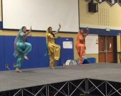 Ashveen Matharu (middle) performing Bhangra at a high school assembly.