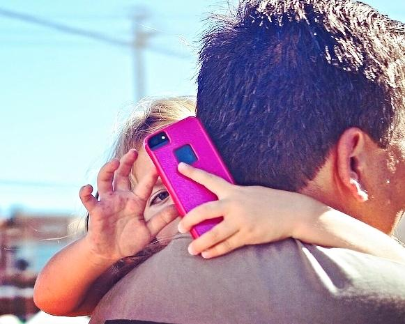 A little girl looks over her father's shoulder at a smartphone.