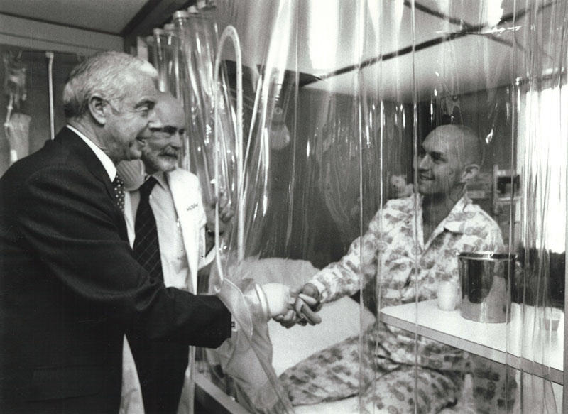 Joe DiMaggio, Dr. E. Donnall Thomas, and patient Darrell Johnson in LAF (laminar airflow) room, 1978