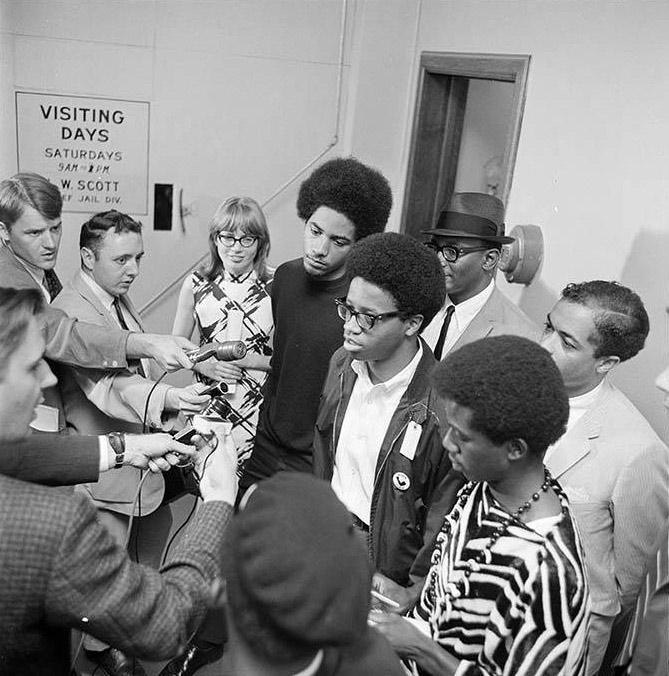 In this photo, defendants (left to right) Aaron Dixon, Larry Gossett, and Carl Miller speak to the press at King County jail some time after their arrest for unlawful assembly in connection with the Franklin High School sit-in, March 1968.