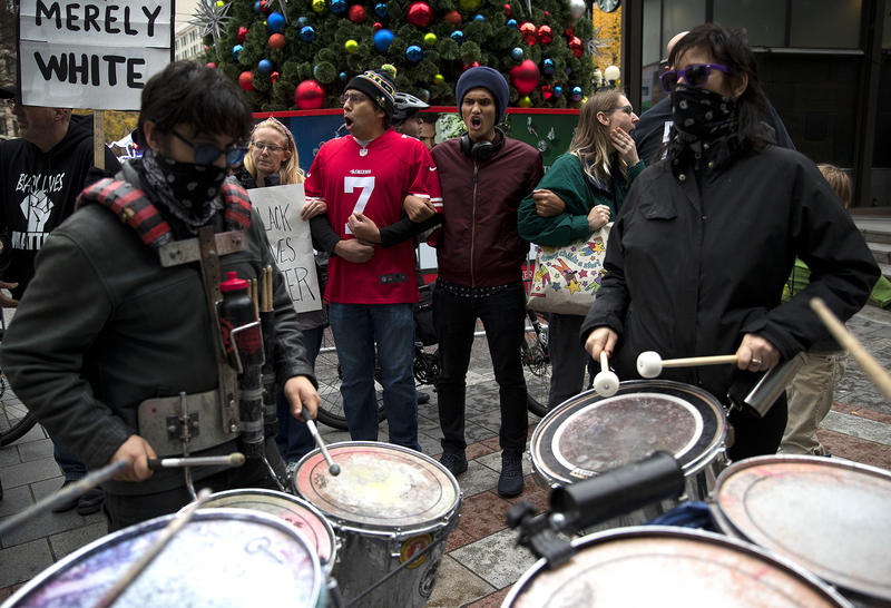 Protesters including Omar Osman, center right, chant during a Black Lives Matter rally on Friday, November 24, 2017, in front of Westlake Center, in Seattle.