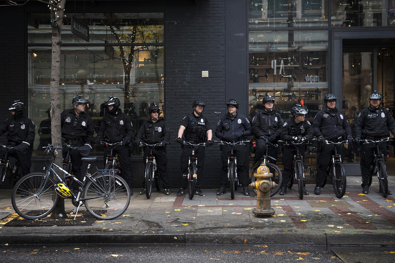 Police officers stand near the intersection of 5th and Pine Streets on Friday, November 24, 2017, during a Black Lives Matter rally in Seattle.