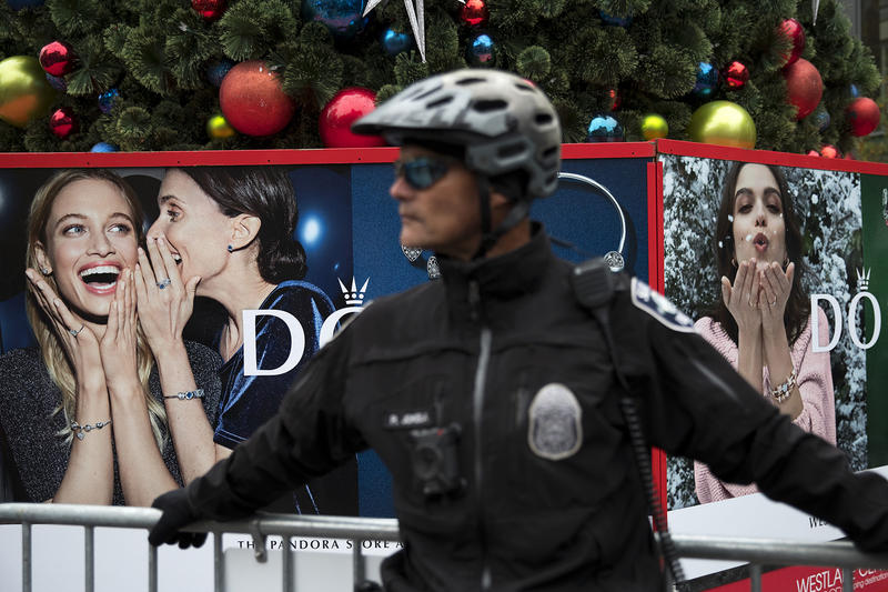 A police officer stands in front of the Christmas tree at Westlake Center on Friday, November 24, 2017, during a Black Lives Matter rally in Seattle.