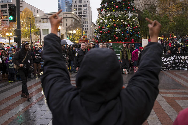 A protester raises two middle fingers in the air during a Black Lives Matter rally on Friday, November 24, 2017, in front of Westlake Center in Seattle.