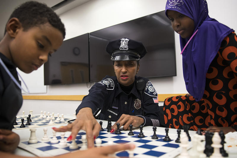 "From left, Kirubel Daniel, 8, Detective Denise ""Cookie"" Bouldin and Deeqo Abdullahi, 11, play a game of chess on Tuesday, November 28, 2017, at the Rainier Beach Library in Seattle."