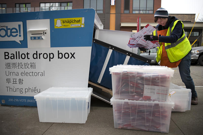 FILE: King County Elections employee Josephine Ruff unloads a  full ballot drop box outside of the Seattle Public Library in Ballard in November of 2017.
