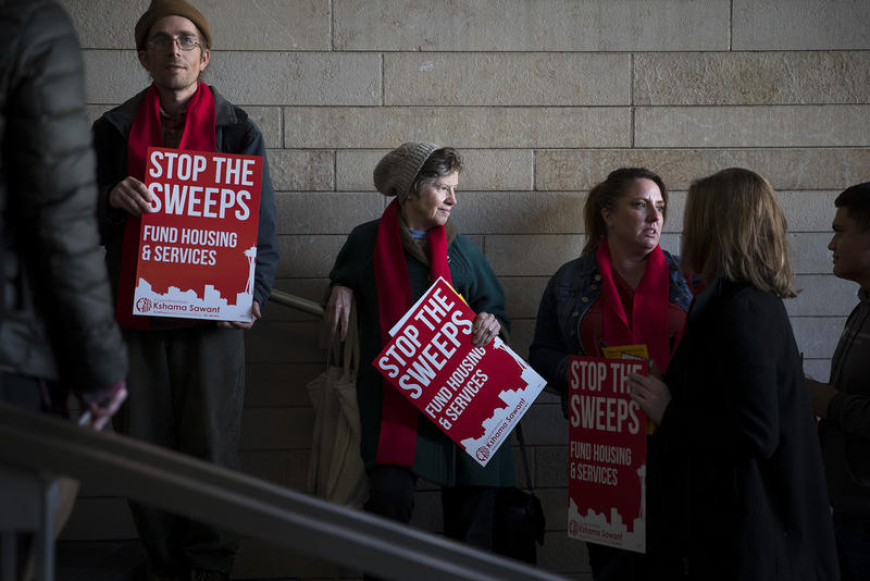 From left, Cory Bushore, Cindy Cole and Jennifer Newman stand in line while waiting to attend the public hearing on Wednesday, November 1, 2017, at City Hall in Seattle.