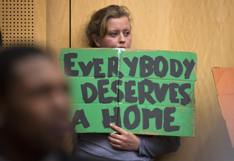 Julia Reed holds a sign during the public hearing on Wednesday, November 1, 2017, at City Hall in Seattle.
