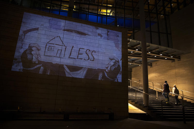 Images are projected onto the side of City Hall on Wednesday, November 1, 2017, during a rally to protest sweeps of encampments in Seattle.