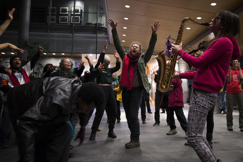 Davis Shoulders, center, dances as Rise Up! Action Band member Adrienne Kerr plays the saxophone on Wednesday, November 1, 2017, during a rally at City Hall in Seattle.