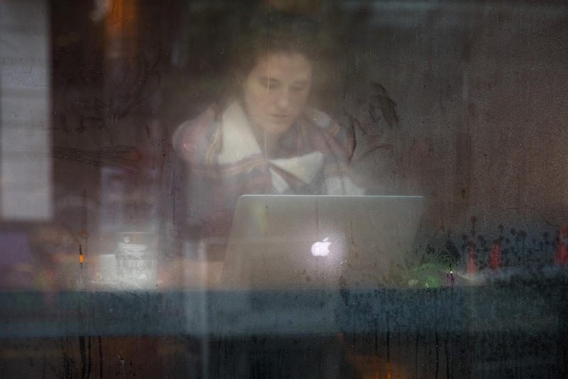 Allison Adams is shown through a foggy window as she works on her laptop at Storyville Coffee on Tuesday, November 21, 2017, on 1st Ave., in Seattle.