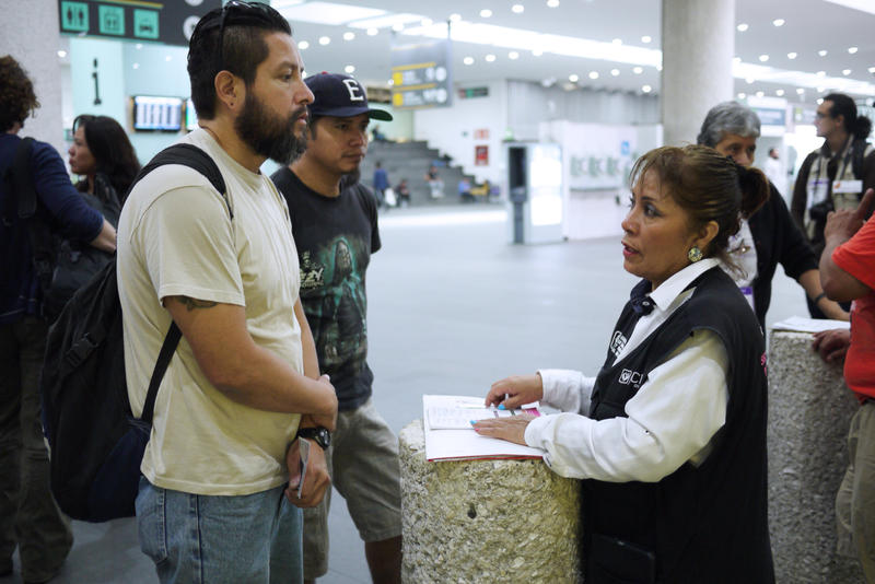 Gustavo Lavariega, a volunteer with Deportees United, talks with an official from Mexico's labor department as he waits for deportees to arrive on a flight from Texas.