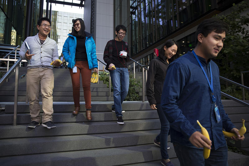 From left, Amazon software development interns Min Vu, Cindy Wang, Jason Mar, Katie Shin and Louis Yang, walk after getting bananas from the Amazon Community Banana Stand outside of the Amazon Meeting Center on Thursday, October 5, 2017, in Seattle.