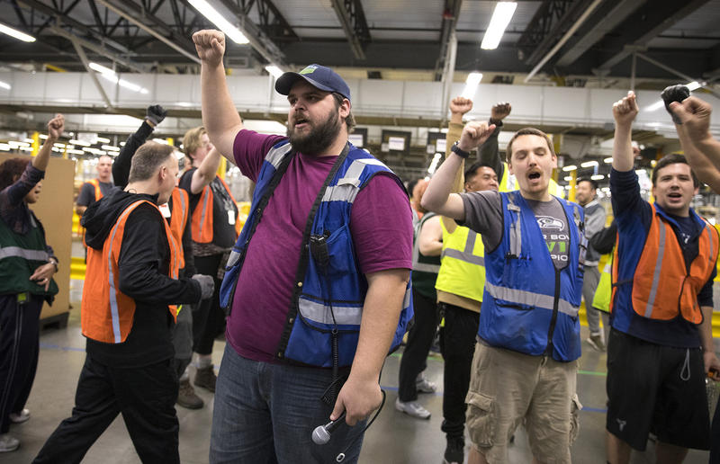 Amazon employee and ship dock manager Zach Mudd, center, leads a group chant as employees return from their lunch breaks at an Amazon fulfillment center on Friday, November 3, 2017, in Kent.