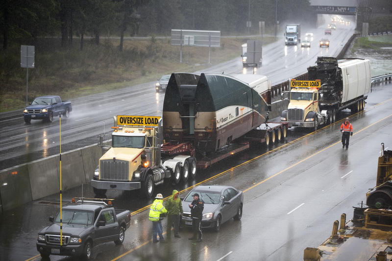 Damaged train cars are loaded onto truck beds along I-5 South on Tuesday, December 19, 2017, in Dupont.