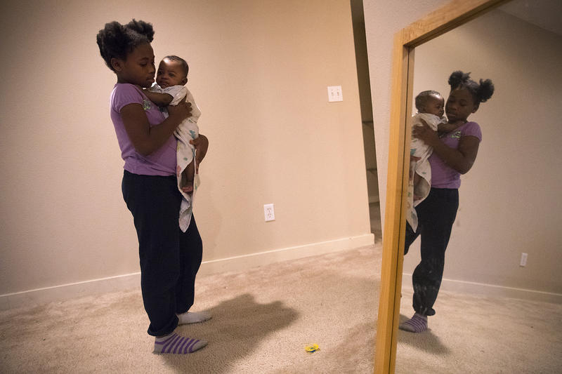 Mariah Hicks pauses while holding her 4-month-old brother, Elijah, after dropping his pacifier, on Wednesday, December 13, 2017, at their apartment in Auburn. `