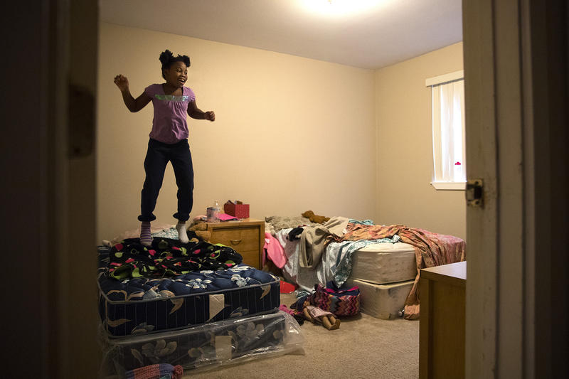 Mariah Hicks jumps on her bed on Wednesday, December 13, 2017, at their apartment in Auburn.