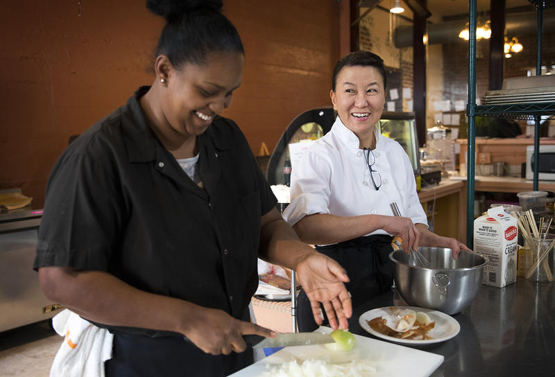 Hiwot Taddesse, left, and Executive Chef Lisa Nakamura laugh while cooking at the Ubuntu Street Cafe on Wednesday, December 13, 2017, in Kent.