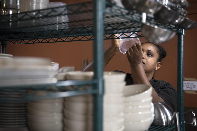 Hiwot Taddesse retrieves a container while cooking at the Ubuntu Street Cafe on Wednesday, December 13, 2017, in Kent.