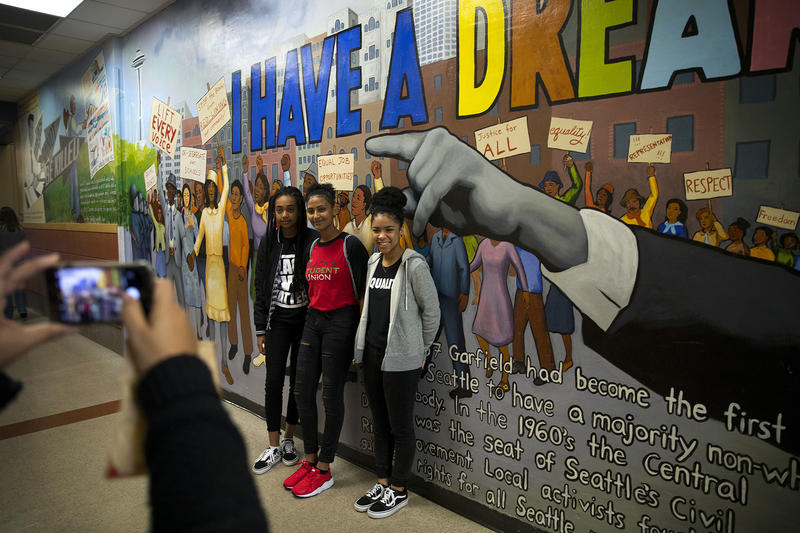 From left, Edom Napoleon, Seati Dirar and Maida Camero pose for a photograph on Monday, January 15, 2018, before a rally at Garfield high school in Seattle.