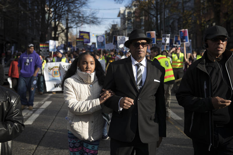 Pastor George Noble marches with his granddaughter, Aleena Edwards, 9, during the annual Martin Luther King Jr. Day march on Monday, January 15, 2018, in Seattle.