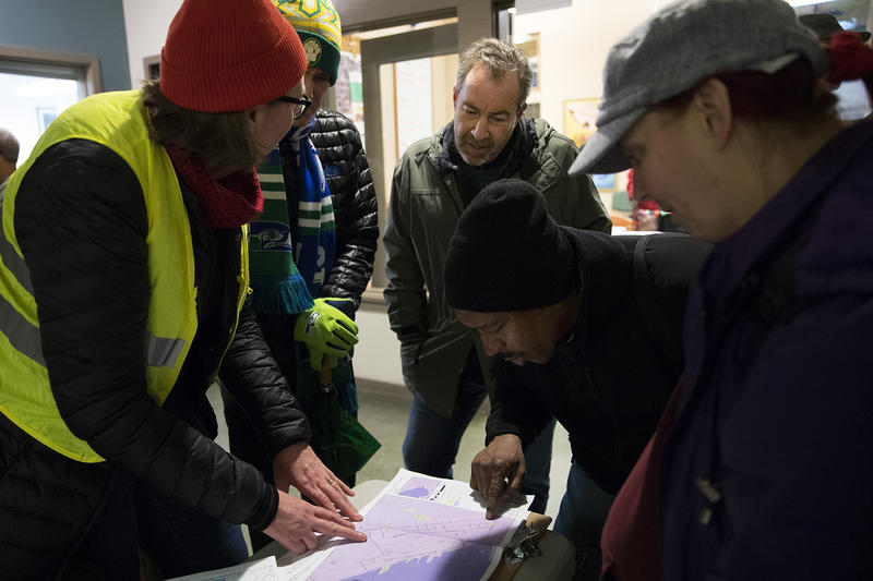 From left, Allison Riese, Mike Hughes, Mark Barbieri, Glenn Coles, and Cate Taylor look at a map before the annual King County Point-In-Time count of people experiencing homelessness on Friday, January 25, 2018, at the Compass Center in Seattle.