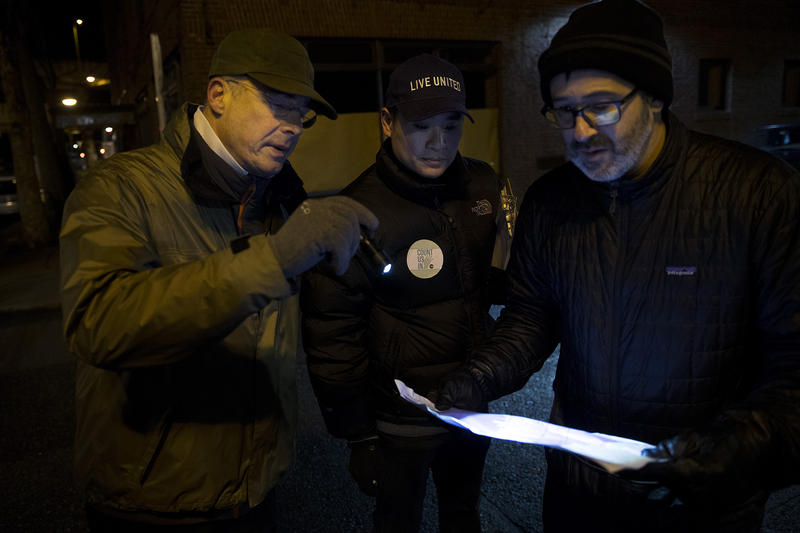 From left, volunteers Peter Orser, Thaddeus Teo and Adam Hasson look at their map during the annual King County Point-In-Time count on Friday, January 25, 2018, in Seattle.