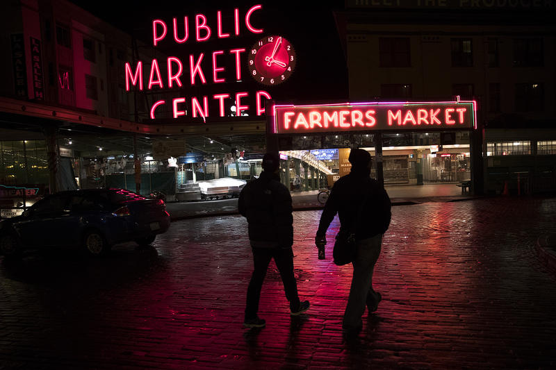Volunteers Thaddeus Teo, left, and Glenn Coles, right, look for people experiencing homelessness during the annual King County Point-In-Time count on Friday, January 25, 2018, in front of Pike Place Market in Seattle.