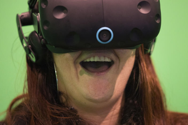 Rachel Booth smiles as she plays a virtual reality game on Friday, November 17, 2017, at Portal Virtual Reality Arcade and Lounge in Seattle.