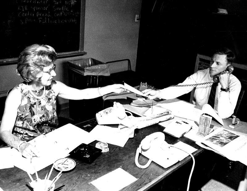 Seattle Rumor Center volunteer Margaret Tashian hands a memo to center director Warren Henderson in this archival photo from July 1969.