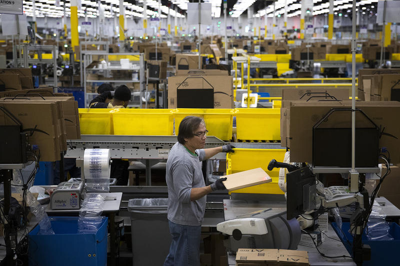 Amazon employee Filomeno Saya packages items at an Amazon fulfillment center on Friday, November 3, 2017, in Kent.