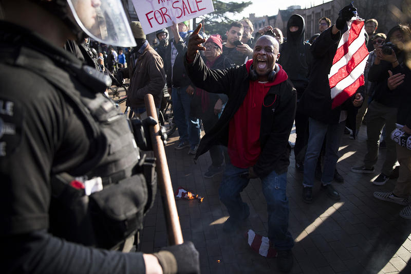 Jamal X, center, yells at police officers after lighting a portion of an American Flag on fire while protesting outside of a College Republicans rally on Saturday, Feb. 10, 2018, at Red Square on the University of Washington campus in Seattle.