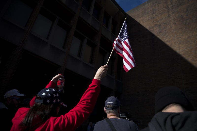 A woman raises an American flag in the air on Saturday, Feb. 10, 2018, at a College Republicans rally at Red Square on the University of Washington campus in Seattle.