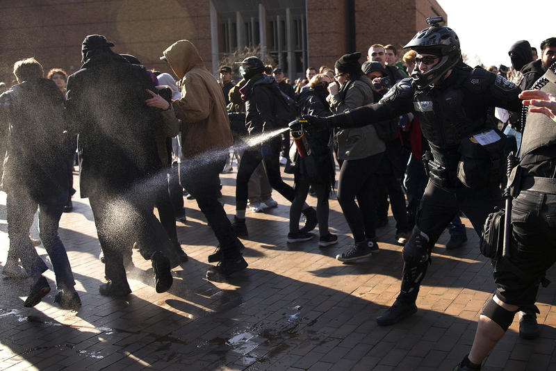 A police officer pepper sprays a group of protesters on Saturday, Feb. 10, 2018, outside of a College Republicans rally at Red Square on the University of Washington campus in Seattle.