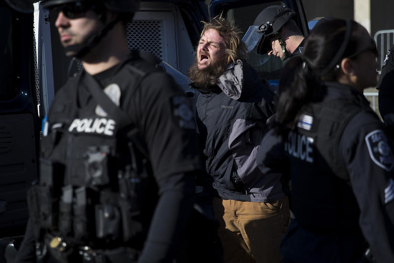 A protester is arrested on Saturday, Feb. 10, 2018, outside of a College Republicans rally at Red Square on the University of Washington campus in Seattle.