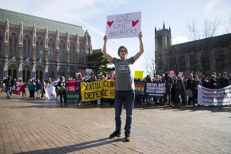 Corbin Gronlie holds a sign toward the College Republicans rally goers on Saturday, Feb. 10, 2018, at Red Square on the University of Washington campus in Seattle.