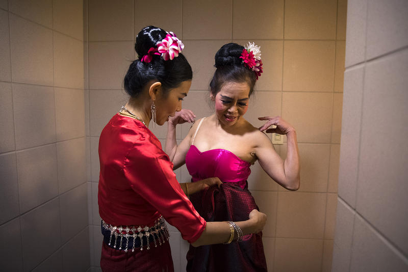 Thai Dance Team member Nuden Bunchomphu, left, helps Uboonwana Teamkitti as the team got ready before performing during the Lunar New Year celebration on Sunday, Feb. 11, 2018, in the Chinatown-International District in Seattle.
