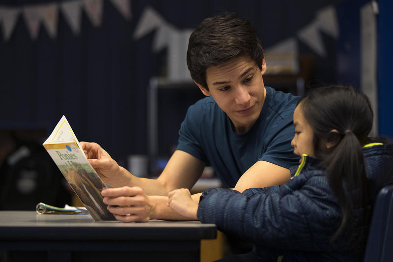 Volunteer Anthony Lee reads with Elizabeth Rith on Wednesday, January 24, 2018, at Sanislo Elementary School in West Seattle.