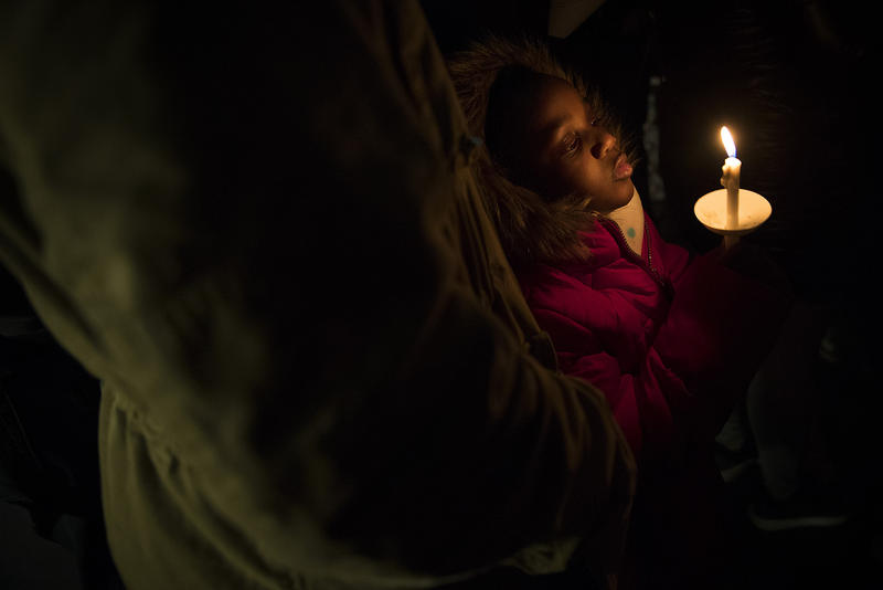 Vivienne Thompson, 6, looks into a candle during a healing and justice vigil honoring DeShawn Horne on Saturday, Feb. 3, 2018, at Harborview Park in Seattle.