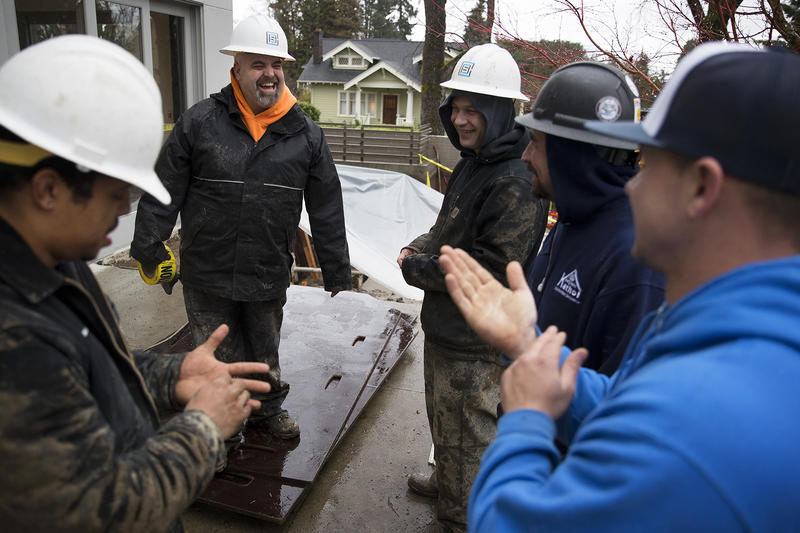 From left, Anthony Banks, Zack Larson, Chris Chase, Devin Ottesen and James Kennemer laugh while working on a job site on Tuesday, January 9, 2018, on 38th Ave East in Seattle.